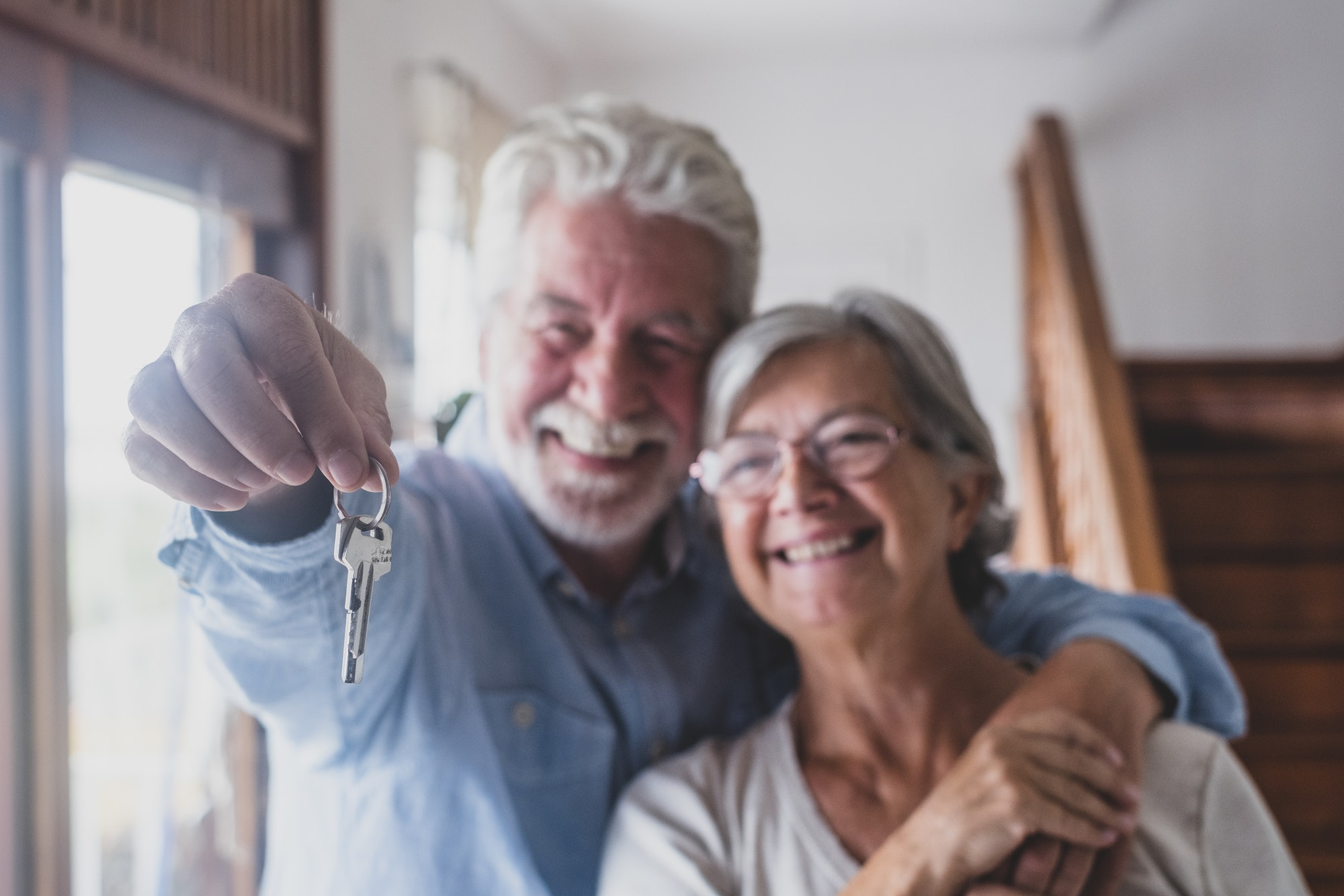Happy senior old aged woman and man customer landlord hold key to new house